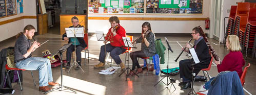 Group of six people sitting in a hall playing instruments