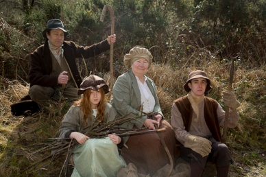 Four people in nineteenth century rural costume sitting on a bank