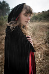 Young woman with long hair, in black cloak with red lining