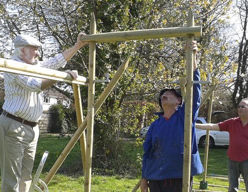 Three men building wooden frames