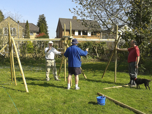 Three men putting together wooden frames