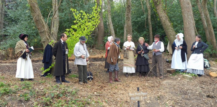 Group of people in nineteenth century costume in a woodland setting