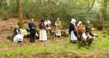 Group of people in nineteenth century costume, in a clearing