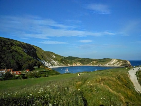 View of Lulwoth Cove, with blue sea, blue sky and green grass in the foreground